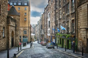 A street scene. Cobbled roadway between five and six storey heritage buildings with Scottish flags flying