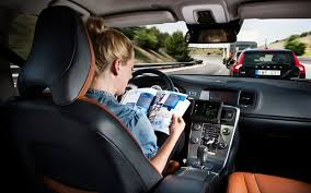 A woman with blonde hair sits reading a magazine resting on the steering wheel of the car she is (not) driving. The road and other cars are visible through the windscreen as the photo was taken from the back seat.