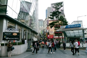 A pedestrian street scene in Seoul with a bookshop on one side and entry to a train station on the other. Tall buildings can be seen in the background. People are going about their daily business.