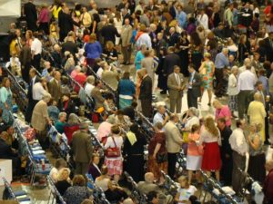 Aerial view of a crowded conference scene where the session has finished and people are standing, sitting and walking about.