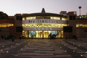 Picture taken at twilight of a building with the name New Town Plaza with Chinese characters underneath. There is a large paved area in the foreground and a few people near the building