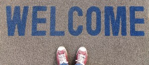 A mid grey doormat viewed from above with the word welcome in blue. At the bottom of the picture you can see the tops of a pair of red and white sneakers. Creating inclusion for everyone.