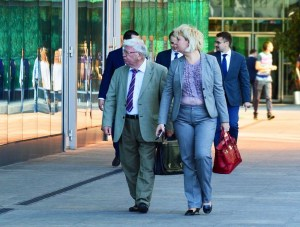 An older man carries a briefcase and looks in the window of a commercial building. A younger blonde woman carries a large red bag and is wearing a blue suit.