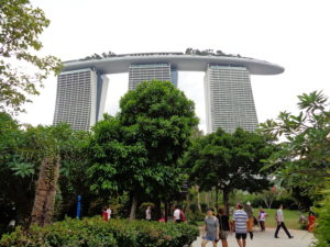 A distance pic of a three column building in Singapore with trees and people in the foreground
