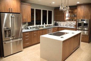 Picture shows a kitchen in timber tones. There is an island bench with an induction cooktop. Drawers replace cupboards