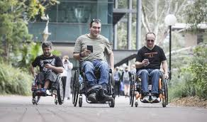 Three manual wheelchair users with their phones