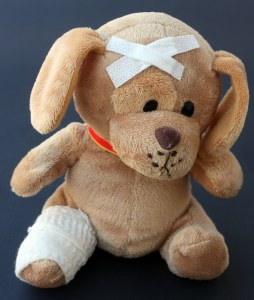 A light brown teddy bear has a bandaged leg and two band aids in a cross on its head