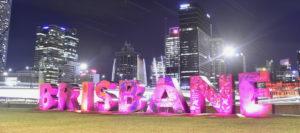 Night scene over Brisbane river with bright pink upper case lettering saying Brisbane.