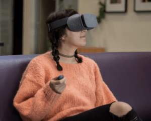 a young woman sits on a couch holding a controller in her hand. she is wearing the virtual reality headgrear.