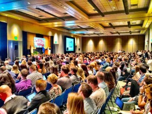 picture of a large audience watching a presentation.