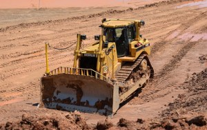 A yellow bulldozer is pictured against bare orange ground