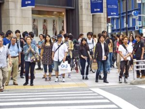 people stand on the footpath waiting to cross on the pedestrian crossing. The street is in Japan