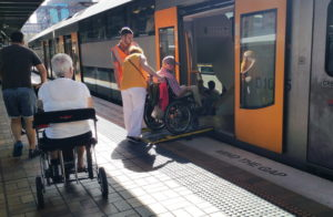 A woman is pushing a man in a wheelchair up a ramp into the train. The train guard looks on. Another woman in a wheelchair waits for her turn. A man with a stroller is also in the picture.