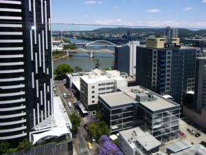 View from high building in Brisbane overlooking building roofs and the Brisbane river and bridges. Jacaranda trees can be seen in the street.
