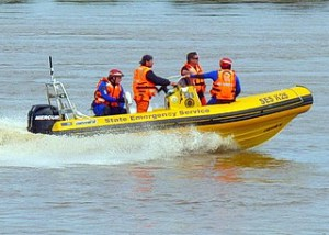Four men with orange lifejackets are standing in a yellow State Emergency Service boat on a swollen river.