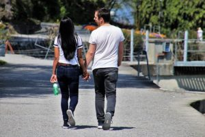 A young woman and young man are walking on a wide concrete path. They are wearing white T shirts and jeans.