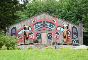 Placed in a rural setting a wooden barn type building displays the cultural icons and two totem poles of the Alaskan Natives