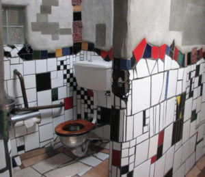 Public toilet in Kawakawa New Zealand. It has large mosaic tiles all at different angles. The toilet seat is timber