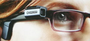 close up of the device sitting on the right arm of the wearer's glasses.