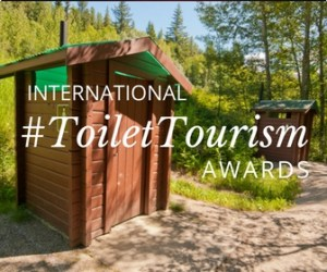 A wooden shack type dunny with the hashtag Toilet Tourism Award