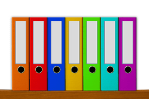 seven ring binders standing upright on a shelf each in a different colour of the rainbow. Universal desingn policy development.