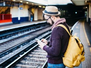 A man stands on a train platform looking at his smartphone. He is wearing a hat and has a bright yellow backpack.