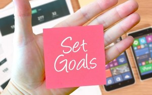 An open palm with a pink post it note with the words set goals