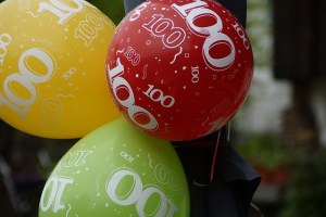 Red Green and Yellow balloons with 100 printed on them in white.