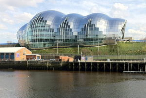 The building is set under a large grey dome shape open at each end. The windows are place so that the many balcony levels show through and at night look like the superstructure of a ship