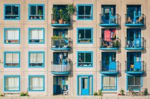 Apartment block with blue windows and balconies with plants and washing drying.