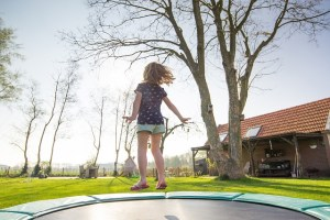 A girl is on a trampoline in a back garden in the countryside.
