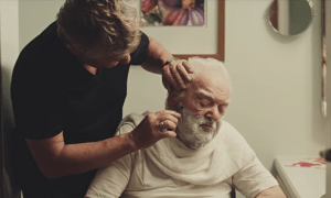 An older man is being shaved by a younger man.