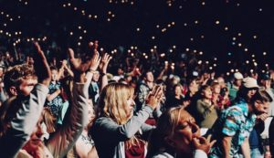 Large crowd clapping and cheering at a nighttime concert
