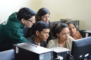 A group of five students cluster around a computer screen. They look as if they are seeing something important.