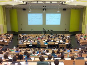 view from the back of a university lecture theatre where students are seated listening to a lecture.