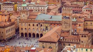 An aerial view of Bologne, Italy showing terracotta roofs and medieval style buildings around a square.
