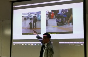Yoshito Dobashi pointing to his slide at the UDHEIT conference showing wheelchair crossing points, one with a man wheeling a suitcase.
