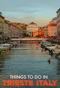 Front cover of a tourist guide showing Trieste at twilight. A scene with buildings and water with small boats.