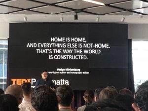 Queenie Tran stands in front of the large display screen, The words are Home is Home and Everything else is not home. That's the way the world is constructed.