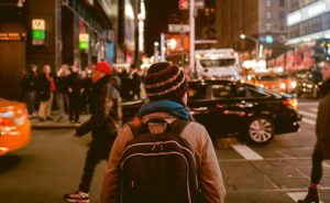 A person wearing a beanie and backpack stands on the footpath. There are people and cars around. It is the evening and street lights are on.