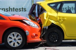 A red car has crashed into the back of a yellow car and crumpled it in the process of a crash test.