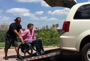Uber driver is pushing a man in a manual wheelchair into the back of the vehicle.