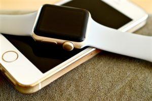An Apple watch is sitting across an Apple iPhone on a desktop.