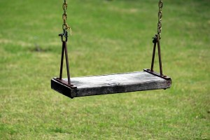 An empty wooden swing hangs over green grass.