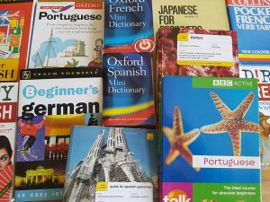 A group of language dictionaries are laid out on a table.