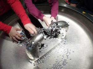 Hands of two children are over a large bowl with lots of little button magnets. They are experimenting through play.