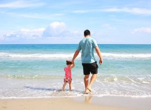 A man holds the hand of a small girl as they wade into the water on the beach. Travel and tourism.