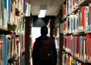 A silhouette of a person between two rows of books on library shelves.
