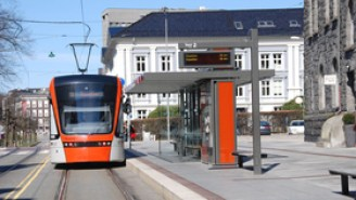An orange tram is arriving at the light rail station.