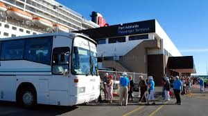 A line pf people are boarding a coach outside a transit building.There is a cruise ship in the backgound.
